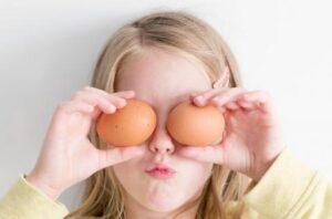 niña con dos huevos sin cocinar